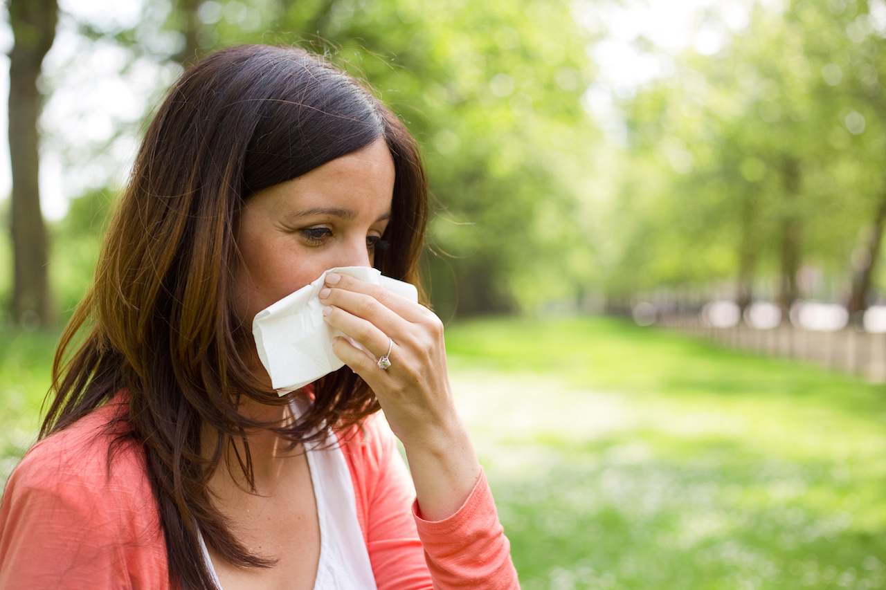 Woman Blowing Nose in KC Park from Springtime Allergies