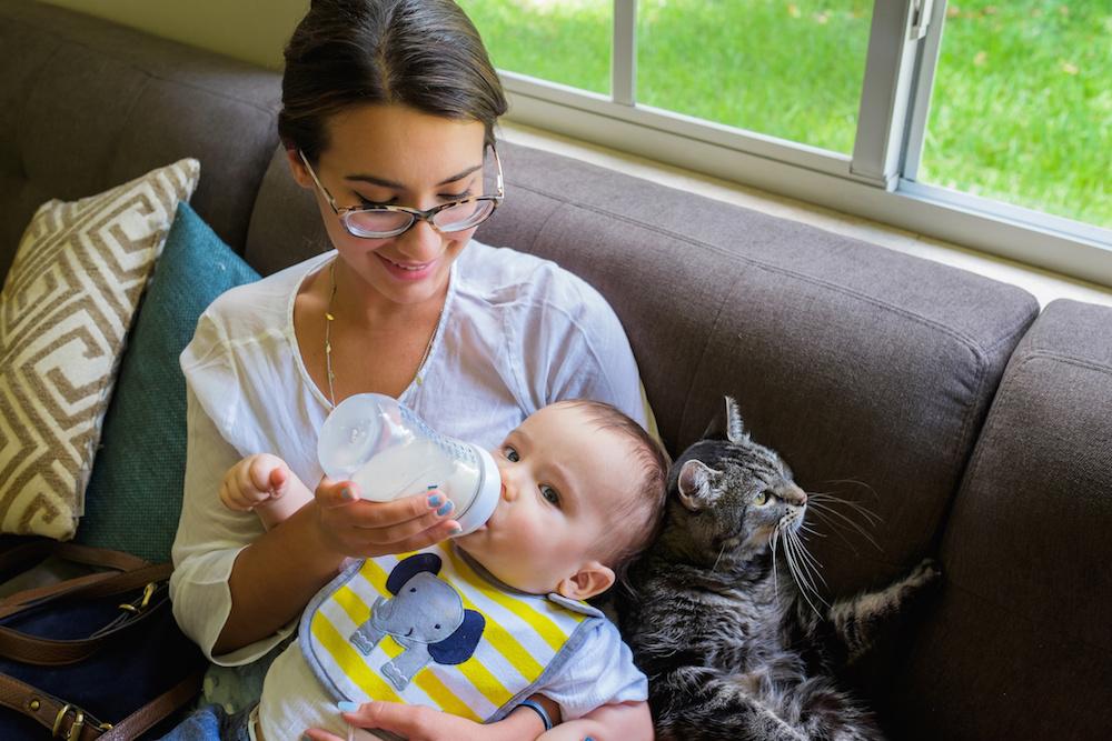 Allergic Mom Bottle Feeding Son Alongside Pet Cat